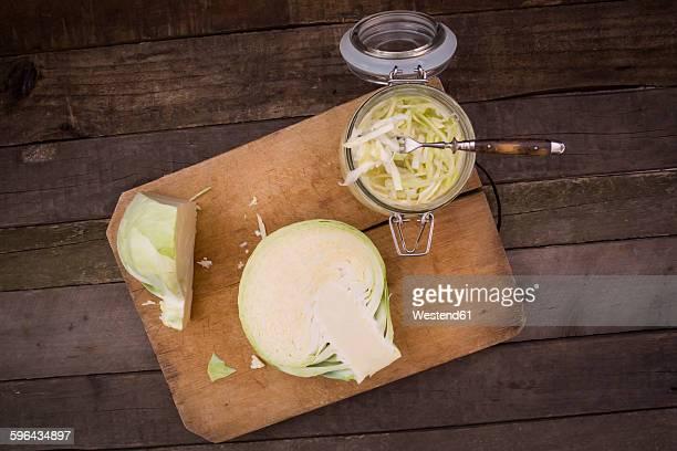 Sauerkraut on chopping board, preserving jar