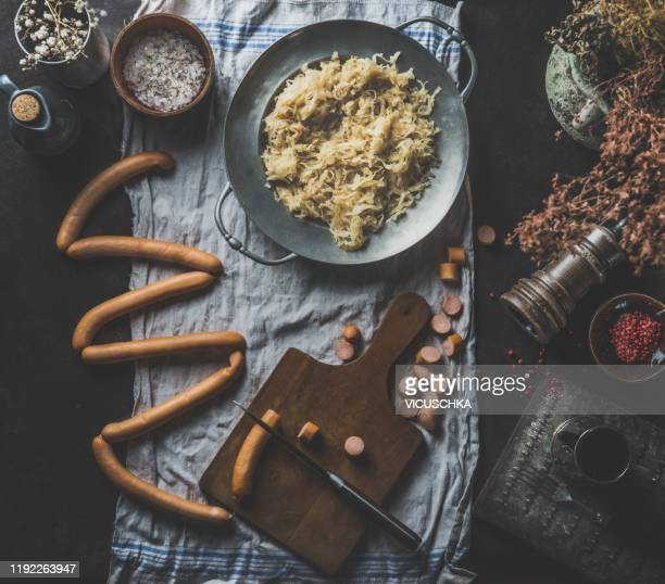 sauerkraut with sausages, cooking preparation - zuurkool stockfoto's en -beelden