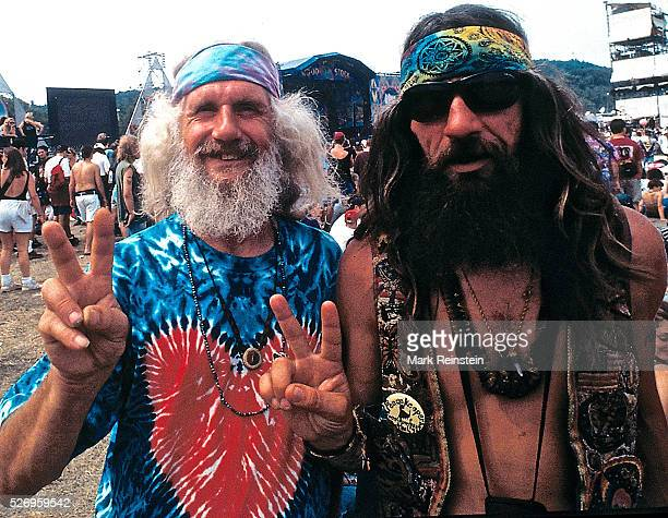 Saugerties New York 8121994 Two older hiipies from the 1969 concert era flash the peace sign Woodstock '94 was a music festival organized to...