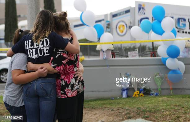 Saugus High School student is embraced as she visits a makeshift memorial in front of the school for victims of the shooting there on November 15...