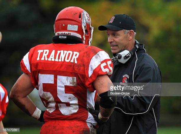 Saugus High senior linebacker Tom Trainor talks with his uncle, linebackers coach and a former Saugus linebacker during a game against Newburyport at...