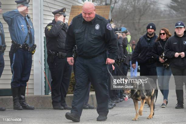 Saugus Police Officer Timothy Fawcett walks into the animal hospital with Bruin as fellow officers and troopers pay their respects After Saugus...