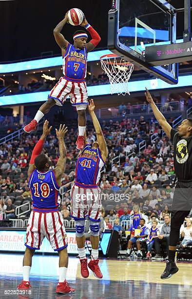 Saul 'Flip' White and Jon 'Hawk' Thomas of the Harlem Globetrotters toss teammate Jonte 'Too Tall' Hall up for a dunk against the World AllStars...