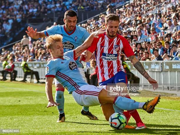 Saul Ñiguez of Atletico de Madrid is challenged by Daniel Wass of Celta de Vigo during the La Liga match between Celta de Vigo and Atletico Madrid at...