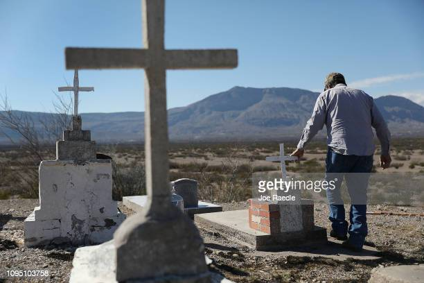 Saul Luna works on cleaning up the Indio Ranch Cemetery which is on a bluff overlooking the border between the United States and Mexico on January 16...