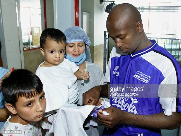 Saul Martinez of the Honduran soccer team signs autographs, 25 July 2001, during a visit to a Red Cross children's hospital at Manizales, Colombia....