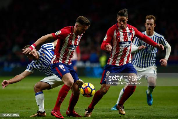 Saul Niguez and his teammate Fernando Torres of Atletico de Madrid compete for the ball with Kevin Rodrigues and David Zurutuza of Real Sociedad de...