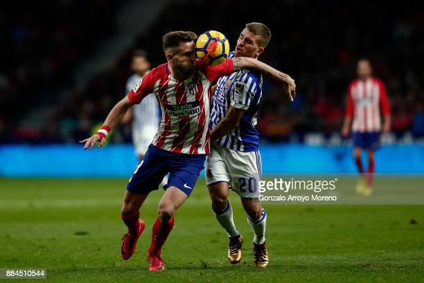 Saul Niguez of Atletico de Madrid competes for the ball with Kevin Rodrigues of Real Sociedad de Futbol during the La Liga match between Club...