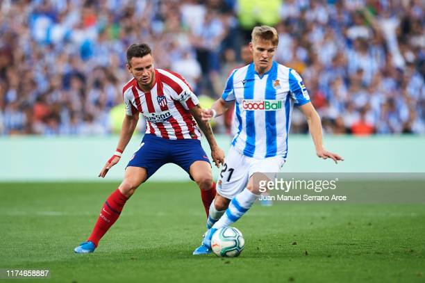 Saul Niguez of Atletico de Madrid competes for the ball with Martin Odegaard of Real Sociedad during the Liga match between Real Sociedad and Club...