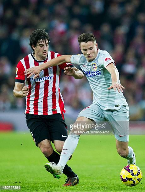 Saul Niguez of Atletico de Madrid competes for the ball with Mikel San Jose of Athletic Club during the La Liga match between Athletic Club de Bilbao...