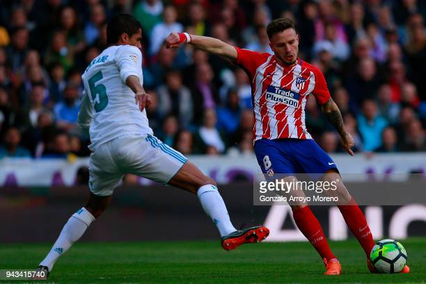 Saul Niguez of Atletico de Madrid competes for the ball with Raphael Varane of Real Madrid CF during the La Liga match between Real Madrid CF and...