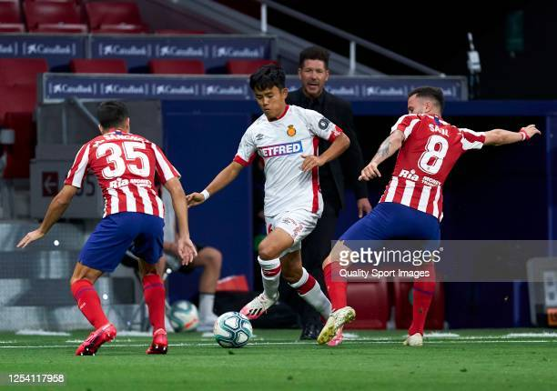 Saul Niguez of Atletico de Madrid competes for the ball with Takefusa Kubo of RCD Mallorca during the Liga match between Club Atletico de Madrid and...