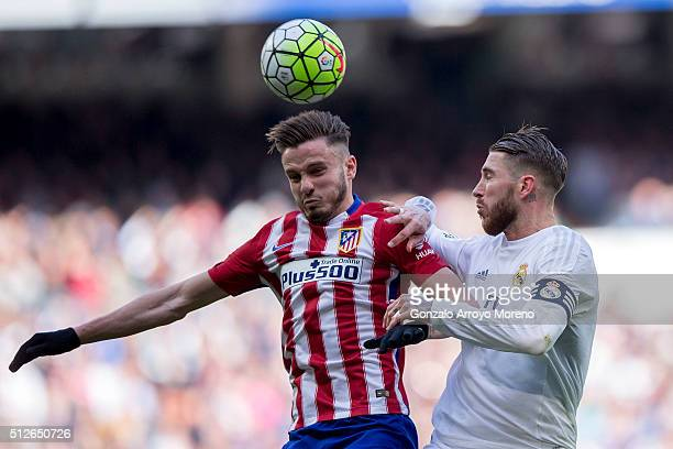 Saul Niguez of Atletico de Madrid wins the header before Sergio Ramos of Real Madrid CF during the La Liga match between Real Madrid CF and Club...