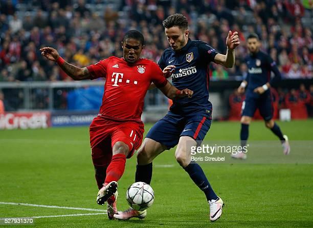 Saul Niguez of Atletico Madrid challenges Douglas Costa of Bayern Munich during UEFA Champions League semi final second leg match between FC Bayern...