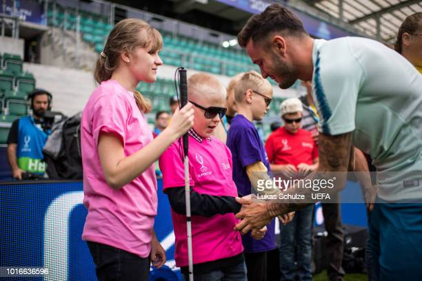 TALLINN ESTONIA AUGUST Saul Niguez of Atletico Madrid greets kids of the UEFA Foundation ahead of Atletico Madrid's training session ahead of the...