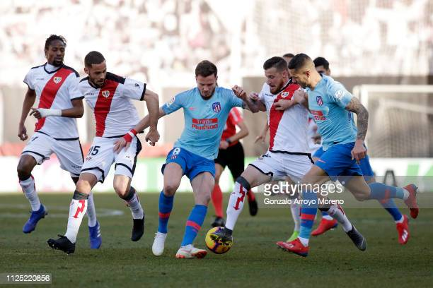 Saul Niguez of Atletico Madrid is challenged by Roberto Triguero of Rayo Vallecano de Madrid and Alex Alegria of Rayo Vallecano de Madrid during the...