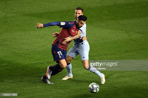Saul Niguez of Club Atletico de Madrid tackles Enric Gallego of CA Osasuna during the Liga match between CA Osasuna and Club Atletico de Madrid at on...