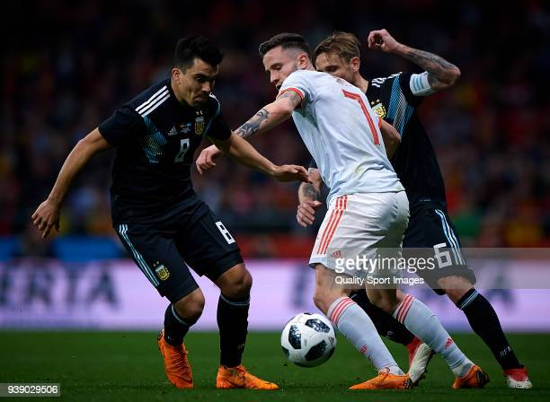 Saul Niguez of Spain competes for the ball with Marcos Acuna and Lucas Biglia of Argentina during the International friendly match between Spain and...