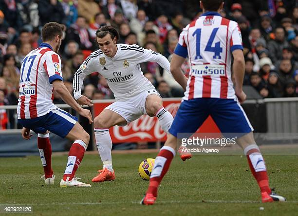 Saul of Atletico Madrid vies for the ball with Bale of Real Madrid during the Spanish La Liga soccer match between Atletico Madrid and Real Madrid at...
