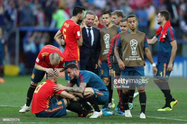 Saul of Spain and Andres Iniesta of Spain console teammate Koke of Spain who looks dejected after missing a penalty in their sides defeat in a...