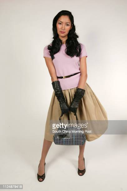 Saule wears a camel poplin skirt black leather belt and long leather gloves from Celine with a pink cashmere sweater from Paule Ka black lace peeptoe...