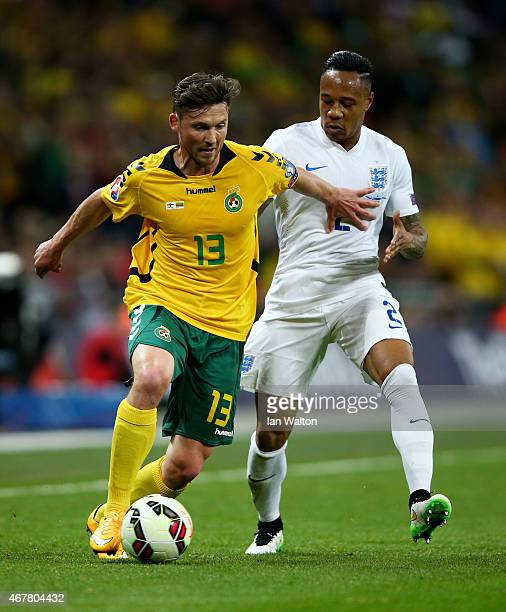 Saulius Mikoliunas of Lithuania is tackled by Nathaniel Clyne of England during the EURO 2016 Qualifier match between England and Lithuania at...