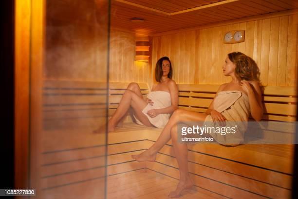 sauna entspannung spa behandlung gruppe von freunden drei attraktive junge frauen in der sauna sitzen - sauna stock-fotos und bilder