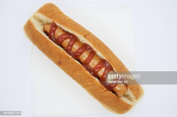 sausage in a bun with tomato sauce isolated on a white background flat lay - rafael ben ari fotografías e imágenes de stock