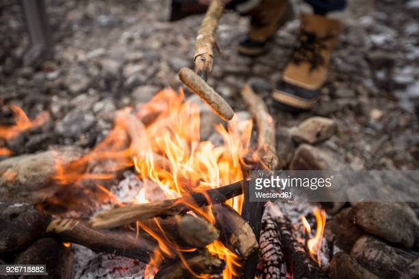 sausage over camp fire - lagerfeuer stock-fotos und bilder
