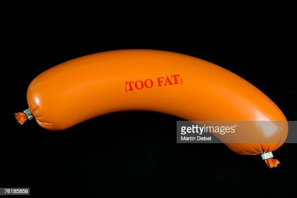A sausage wrapped in plastic packaging and stamped 'Too Fat'