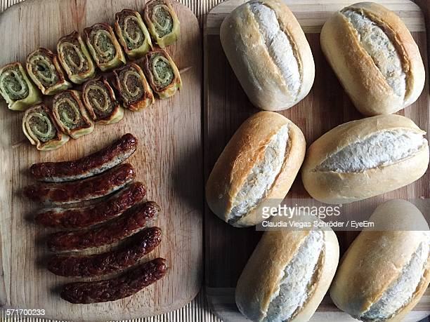 Sausages, Buns And Garlic Bread On Cutting Board