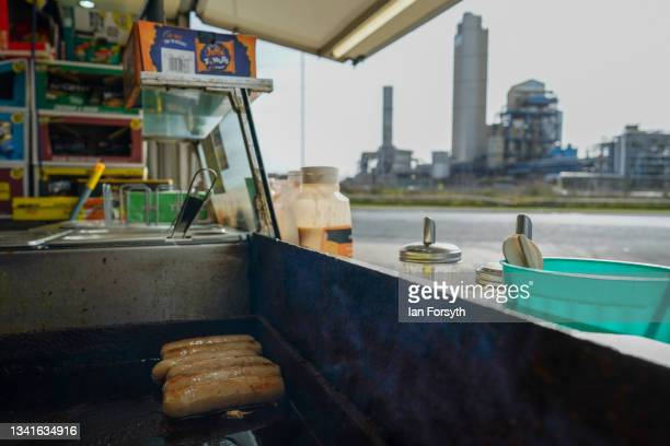 Sausages cook on the grill of a roadside cafe in the shadow of the CF Fertilisers site on September 21, 2021 in Billingham, England. Britain's...