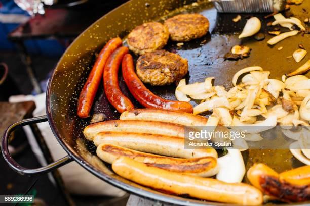 sausages cooking in a big frying pan on portobello road market, notting hill, london - alimentação não saudável imagens e fotografias de stock