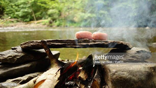 sausages cooking over campfire by river - ウッファリーズ ストックフォトと画像