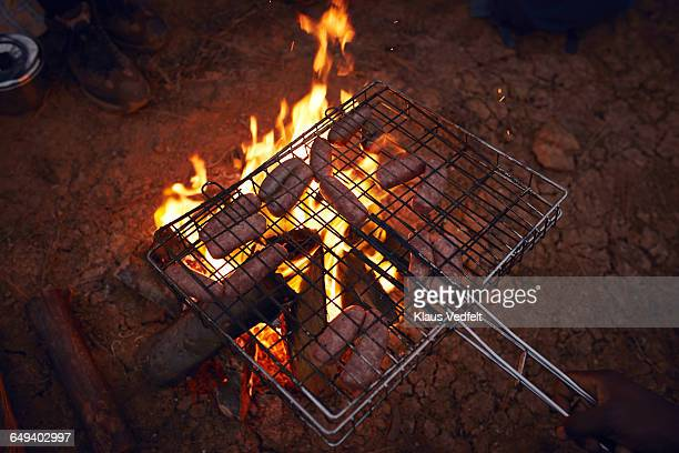 Sausages getting grilled on the bonfire