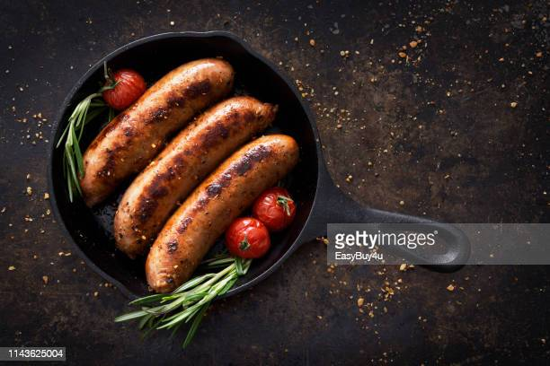 sausages in a skillet - sausage stock pictures, royalty-free photos & images