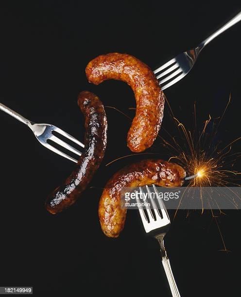 Sausages on forks.