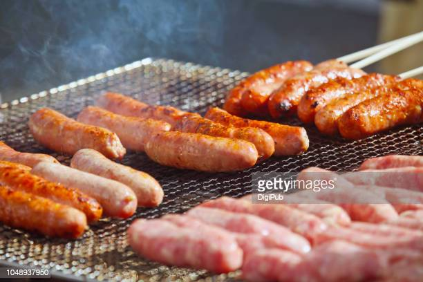 sausages on grill grate being grilled on the street at event - 九月 ストックフォトと画像