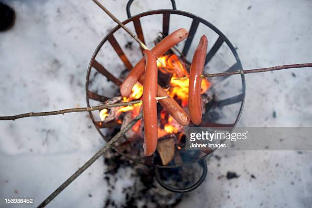 Sausages on sticks above fire