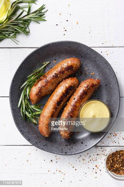 sausages with dijon mustard sauce and seasoning - sausage stock pictures, royalty-free photos & images