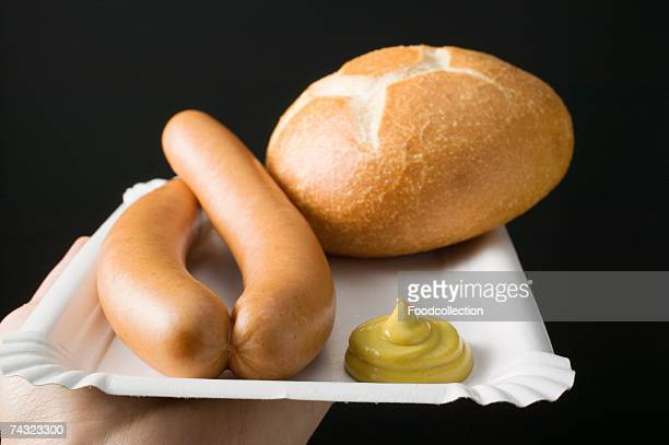 Sausages with mustard and roll on paper plate