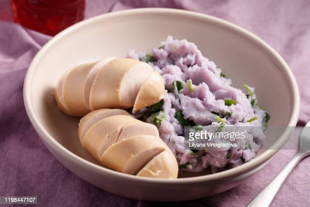 sausages with traditional dutch dish stamppot mashed purple potatoes with spinach - stamppot stockfoto's en -beelden