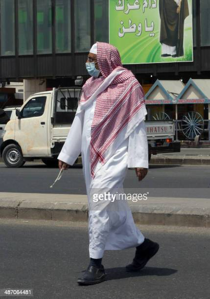A Sausi man wears a mouth and nose mask as he walks in a street of the Red Sea coastal city of Jeddah on April 27 2014 The MERS death toll in Saudi...