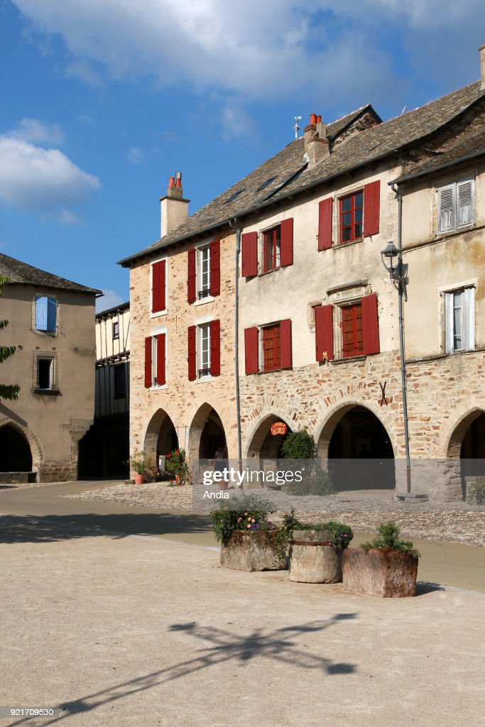 traditional houses in the square 'place de la Bastide'. Facades of traditional houses and arches of the former Royal bastide. The village is registered as one of the 'Plus Beaux Villages de France' (Most Beautiful Villages of France). Shadow of a cross in the square.