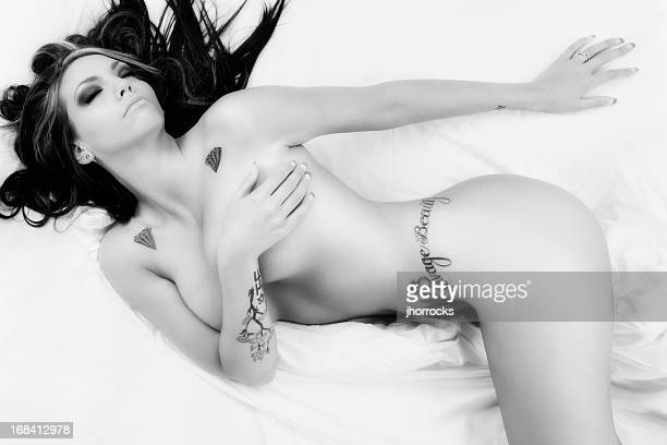 Savage Beauty: Black and White Tattooed Nude Woman on Bed