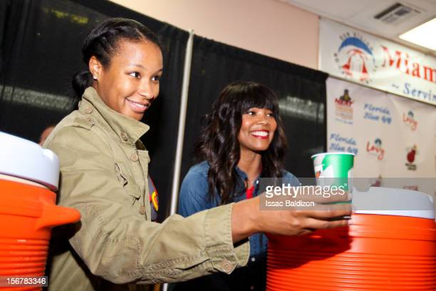 Savannah Brinson left fiancée of LeBron James of the Miami Heat and actress Gabrielle Union girlfriend of Dwyane Wade of the Heat serve drinks during...