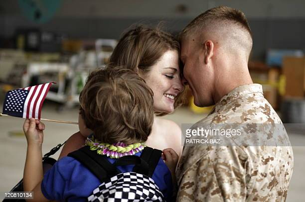 Savannah Dejong holding her son Rhone greets her husband Daniel with 1/3 Marines Bravo Company upon his return to Hawaii on June 13 following a...