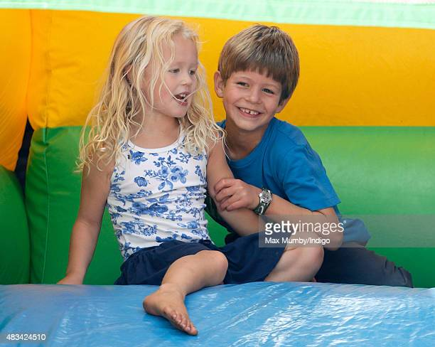 Savannah Phillips and James Viscount Severn play on an inflatable slide as they attend day 2 of the Festival of British Eventing at Gatcombe Park on...