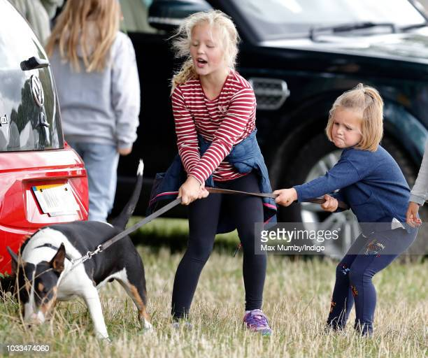 Savannah Phillips and Mia Tindall struggle to control their grandmother's bull terrier dog as they attend the Whatley Manor Horse Trials at Gatcombe...