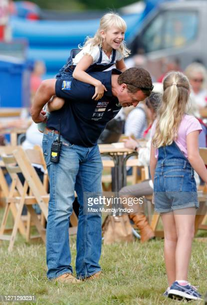 Savannah Phillips looks on as Peter Phillips gives daughter Isla Phillips a piggyback on day 1 of the 2019 Festival of British Eventing at Gatcombe...